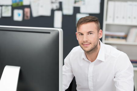 Young businessman sitting at his desk in the office in front of a large desktop computer looking at the camera with a smile