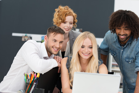 young business people: Happy multiethnic diverse group of young business people grouped around a laptop computer smiling as they look at data on the screen