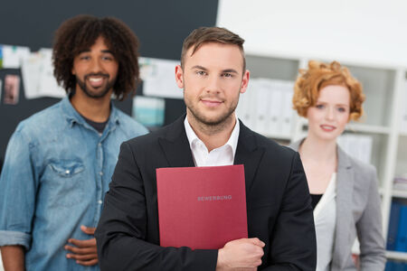 Successful male job appplicant standing in a suit holding a file with his CV flanked by two mutliethnic colleagues photo