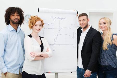 Happy successful business people standing grouped around a flip chart during an in house training session and presentation, men and women present photo