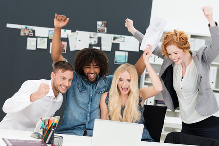 Successful attractive young multiethnic business team celebrating a victory cheering and pumping the air with their fists