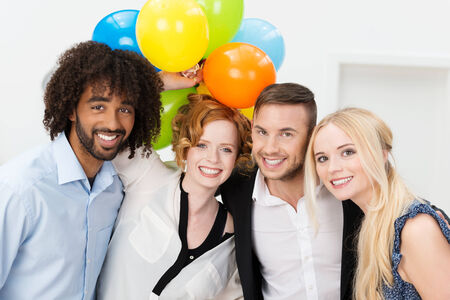 company party: Partytime at the office with a group of rather dishevelled young business peole smiling and laughing at the camera while holding a large bunch of colorful balloons Stock Photo