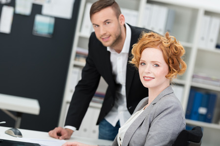 Attractive redhead businesswoman with a lovely friendly smile sitting at her desk in the office working a male colleague standing over her photo