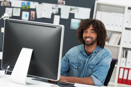 afro hairdo: Charismatic African American businessman with an afro hairdo sitting at his desk with a desktop monitor smiling at the camera