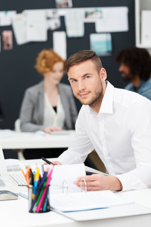 Attractive young businessman in a busy office sitting working at paperwork on his desk looking up at the camera photo