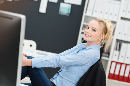 Young businesswoman relaxing at her desk sitting back in her chair at the office with her feet up smiling at the camera Stock fotó