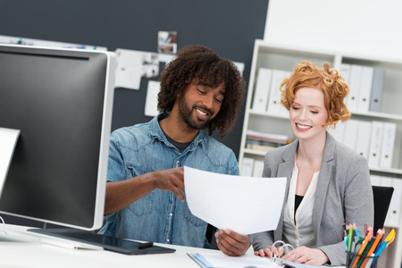 togther: Happy Afro American businessman discussing a document with a beautiful smiling redhead coworker as they sit togther at a desk in front of a large computer monitor