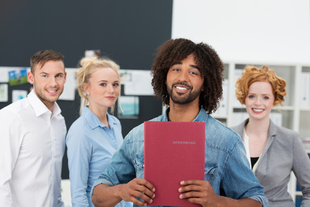 applicant: Smiling modern Afro-American businessman holding his curricukum vitae in a file in front of his chest watched by two co-workers as he prepares for a job interview