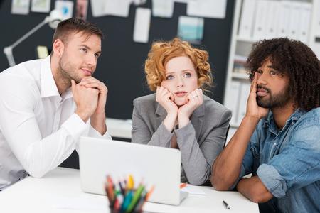 答えを求め、漿液性表現の深い思い入れのあるテーブルに座ってソリューションのための損失で若いビジネス チーム