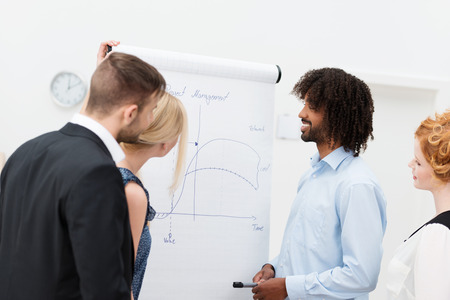 Trendy modern Afro-American standing with his co-workers in front of a flip chart smiling as he discusses the charts with them Stock Photo - 28756831