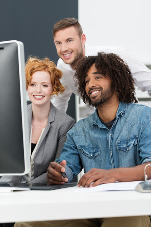 Happy African American man at work smiling as he sits with his colleagues in the studio at a computer creating a new innovation or design photo
