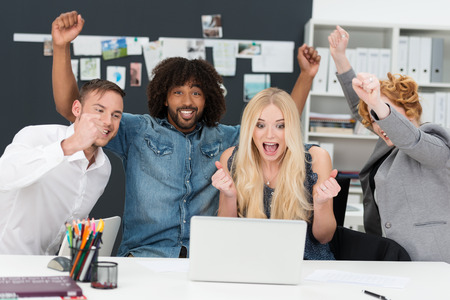 group goals: Young multiethnic business team cheering as they sit grouped around a laptop computer celebrating a success