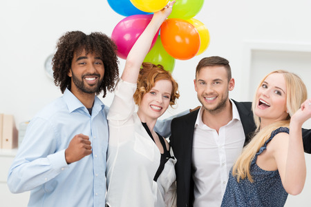 company party: Happy group of business friends partying smiling and laughing at an office party with a large bunch of colorful balloons