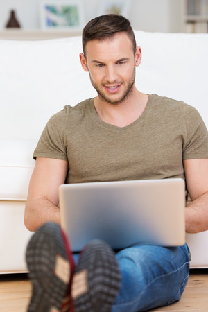 computer user: Young man smiling as he reads his laptop computer screen while relaxing on the hardwood floor in his living room at home Stock Photo