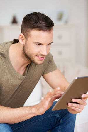 Interested attractive young man sitting on a sofa staring intently at his tablet computer as he navigates the web photo