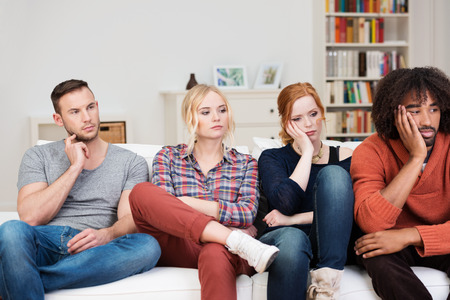 glum: Bored group of multiracial friends relaxing at home sitting in a row on a comfortable sofa watching something off screen to the right with glum expressions Stock Photo