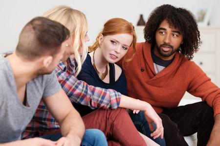 Grupo de jóvenes amigos multirraciales tener un debate serio sentado en una fila en un sofá que se inclina hacia adelante para mejorar la comunicación Foto de archivo