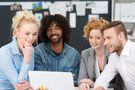Young business team working together sitting grouped around a smiling African American colleague in a casual denim shirt as they work on a laptop computer photo