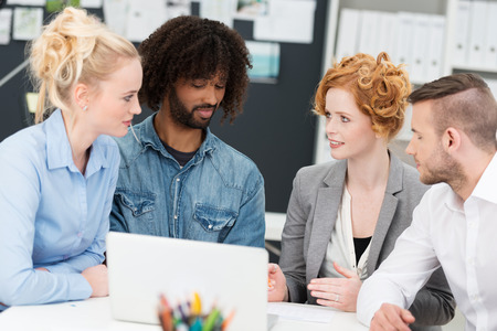 Multiethnic diverse young business team sitting having a serious discussion as they discuss information on a laptop computer photo