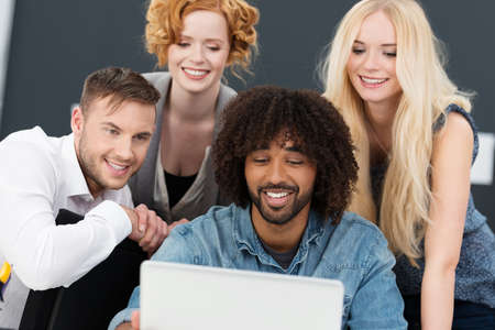 Creative multiethnic young group of business partners working together on a laptop computer grouped around a smiling African American man photo