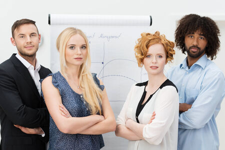 Serious young group of business men and women standing facing the camera with folded arms in front of a flip chart photo