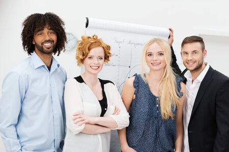 Confident happy multiracial young business team posing together in front of a flip chart after a brainstorming session photo