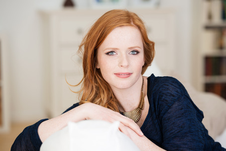 Beautiful serene young redhead woman relaxing at home on a comfortable settee looking at the camera with a friendly smile Imagens