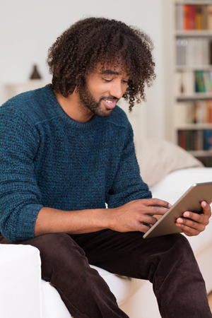 Young African American man using a tablet as he sits relaxing at home on a sofa smiling as he surfs the internet photo