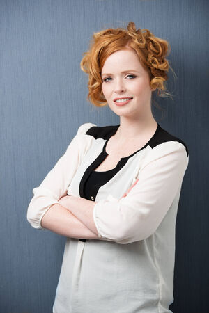 Beautiful stylish redhead woman standing against a grey studio background with folded arms looking at the camera with a quiet smile photo