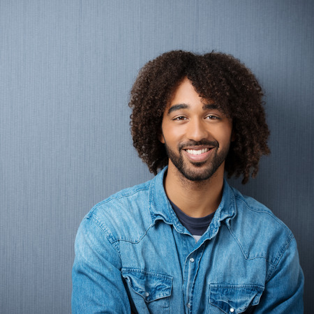 happy young man: Happy young African American man with a big friendly smile and curly afro hairdo, upper body against a grey studio background Stock Photo