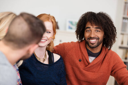afro hairdo: Multiracial young group of friends sitting relaxing at home with focus to a handsome young African American man with a friendly smile and curly afro hairdo