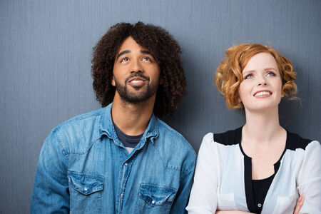 two visions: Young attractive multiethnic couple smiling as they stand daydreaming and planning for the future, against a grey background Stock Photo