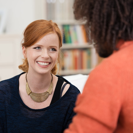 first sight: Stylish happy young redhead woman chatting to a young African American male friend in the living room