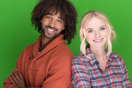 Smiling young multiracial couple with a hip African American man and cute blond woman standing shoulder to shoulder smiling at the camera on a green background photo