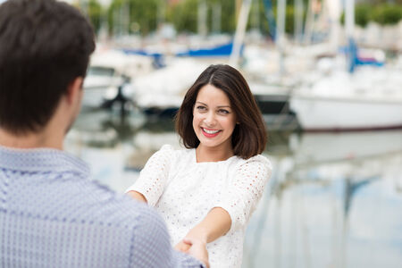 citytrip: Smiling young woman holding the hands of her beau and leaning backwards with a look of loving happiness against a marine harbour background