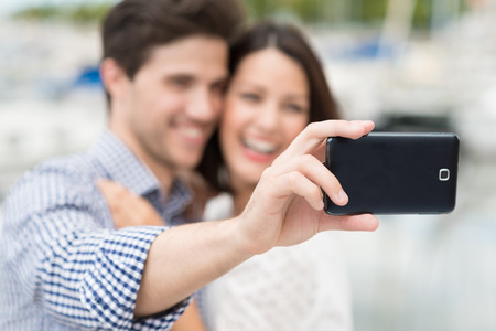 Happy young couple taking a self portrait laughing as they pose for the camera on their mobile phone, focus to the phone photo