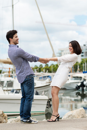 citytrip: Energetic young couple on a quay overlooking boats in a harbour laughing and holding hands and leaning back pulling against each other