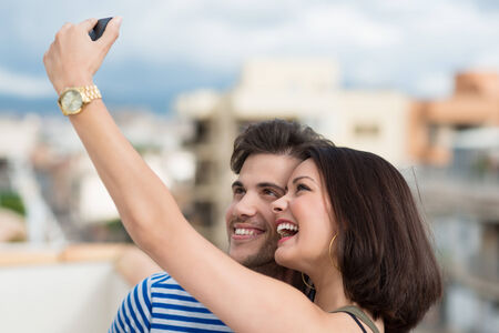 citytrip: Beautiful vivacious young couple taking a self portrait on their mobile phone posing close together laughing at the camera