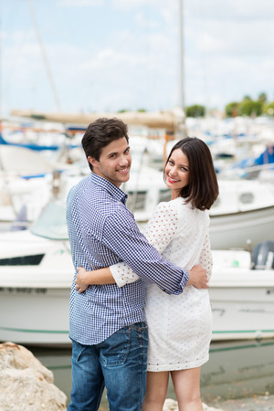 citytrip: Attractive young couple standing arm in arm overlooking a marine small boat harbour turning back to smile at the camera Stock Photo