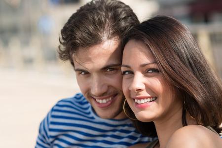 jovenes enamorados: Retrato de un feliz joven pareja cariñosa posando con las cabezas muy juntas sonriendo a la cámara al aire libre en la luz del sol Foto de archivo
