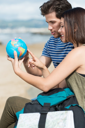Young couple sitting at the beach planning their holiday pointing excitedly at a globe as they choose their next destination Stock Photo - 29563175