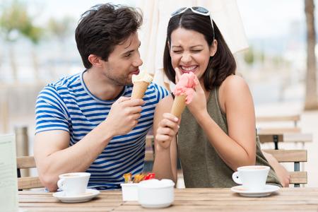 笑的夫妇吃冰淇凌锥体,他们坐在一杯咖啡的一个露天的餐馆在夏天阳光下