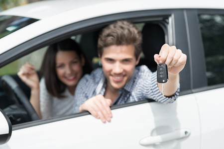 Smiling man holding up the key of his car through the open side window of the vehicle conceptual of ownership , purchase or rental on vacation, focus to the key photo