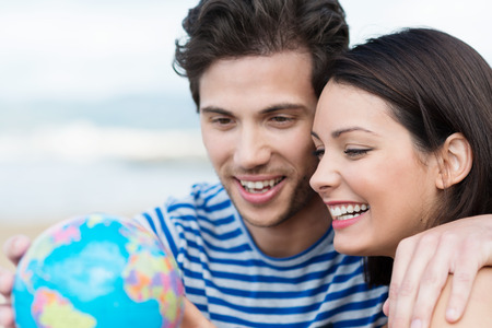Excited attractive young couple looking at a globe as they plan their summer vacation while enjoying a day outdoors in the sun Stock Photo - 29563185