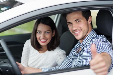chofer: Conductor masculino guapo dando un pulgar hacia arriba a trav�s de la ventanilla del coche mientras conduce, junto con su bella y joven esposa o novia como pasajero