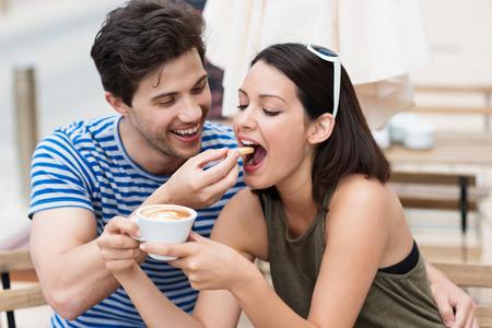 novio: Romántica pareja de jóvenes el consumo de café con el joven riendo alimentar una galleta a su novia o esposa mientras sostiene una taza de capuchino