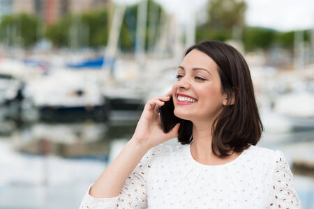citytrip: Beautiful woman smiling as she chats on her mobile phone looking away into the distance with a beaming smile of pleasure, marine harbour in the background Stock Photo