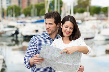 citytrip: Young tourist couple on vacation standing in front of boats in a marina looking up directions on a map in the summer sunshine