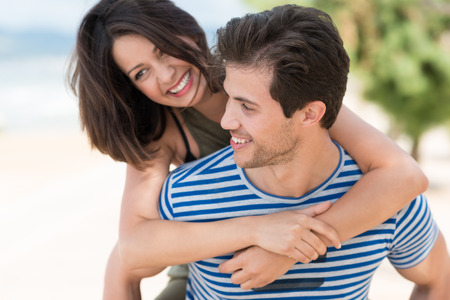 woman from behind: Loving woman hugging her husband from behind with a big beaming smile of happiness as they enjoy a day on a tropical beach together