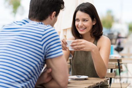 Young woman enjoying a cup of coffee outdoors at a street cafe as she sits chatting to her boyfriend or husband in the summer sun photo